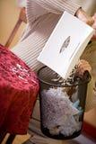 Finanser: Man som dumpar strimlat papper in i avfall Royaltyfri Bild