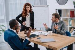 Finansiell konsulent som står nära tabellen med bärbara datorn och legitimationshandlingar medan argumentera för två affärsmän Royaltyfria Bilder