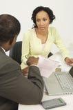 Finansiell rådgivare i diskussion med kvinnan Arkivbild