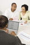 Finansiell rådgivare som använder bärbara datorn med par i diskussion över dokument Arkivbilder