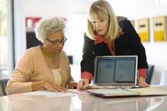 Finansiell rådgivare som hjälper den höga kvinnan Arkivbild