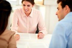 Finansiell rådgivaredam som förklarar ansökningsblankett Arkivfoton