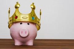 Finansiell vinnare eller konung av pengarbesparingbegreppet som ler den lyckliga rosa spargrisen som bär en guld- krona på trätab royaltyfri fotografi
