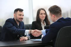 Finansiella partners för handskakning som sitter på tabellen Arkivfoto