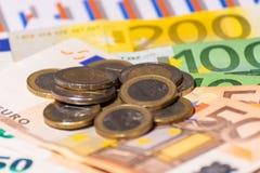 Finansiella rapport, mynt och euroanmärkningar fakturerar pengar Många eurosedlar och staplade mynt arkivfoto
