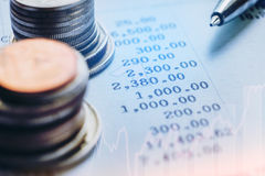 Finansiellt analyserande begreppspenna och mynt och på pappers- rapport Arkivfoto