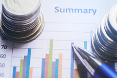 Finansiellt analyserande begreppspenna och mynt och på pappers- rapport Arkivbilder