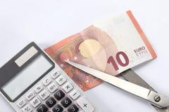 Finansiellt begrepp: klipp skulden en räkning för euro tio, ett par av scissor och en räknemaskin på vit bakgrund med kopieringsu arkivbilder