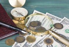 finansiellt begrepp Piska anteckningsboken, reservoarpennan, förstoringsglaset, mynt och kompasset på den gröna wood tabellen Arkivbild