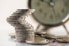 finansiellt besparingbegrepp myntbunt med en klockabakgrund Arkivbild