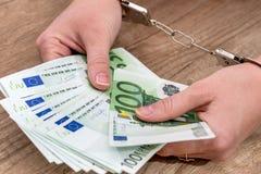 finansiellt brotts- begrepp - kvinnlig hand med handbojor som rymmer euro 100 Royaltyfri Fotografi