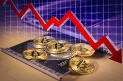Finansiellt fallande begrepp för björnmarknad med Bitcoin mynt över ett CD drev för bärbar dator` s Arkivbilder