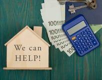 Finansiellt hj?lpande begrepp - litet hus med text som vi kan hj?lpa! , tangenter, r?knemaskin, pass, pengar royaltyfria bilder