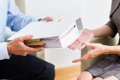 Finansiellt konsultera - kund som räcker över dokument royaltyfria foton