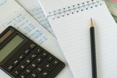 Finansiellt lönmanbegrepp som blyertspennan på den vita anteckningsboken med ca royaltyfri fotografi