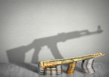Finansieringkrigbegrepp, pengar med vapenskugga Royaltyfri Foto