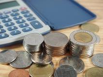Finansowy biznes, stos monety, bahta pieniądze i kalkulator na drewnianym tle, Fotografia Royalty Free