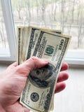 Finansowy pieni?dze Obs?uguje trzyma? sto dolar?w banknoty dla wynajem lub nabywa mieszkanie zdjęcia stock