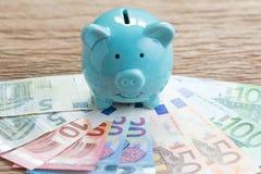 Finanspengarsparkonto, begrepp för Europa nationalekonomi, blå spargris på högen av eurosedlar på trätabellen, framtida tillväxt royaltyfria bilder