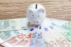 Finanspengarsparkonto, begrepp för Europa nationalekonomi, vit spargris på högen av eurosedlar på trätabellen, framtida tillväxt arkivbild
