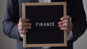Finanza di parola dalle lettere sul bordo del testo in uomo d'affari anonimo Hands video d archivio