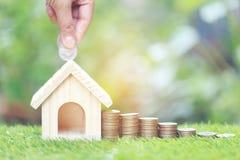 Finanza, pila di soldi delle monete e casa di modello su backgroundd verde naturale, risparmianti per preparare in futuro fotografie stock