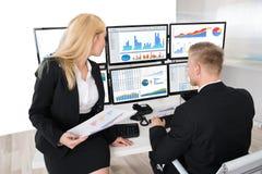 Finanzarbeitskräfte, die Diagramme auf Computern im Büro analysieren Stockfotos