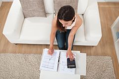 Finanzas calculadoras del hogar de la mujer confiada en la tabla Imagenes de archivo