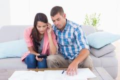 Finanzas calculadoras del hogar de los pares en la tabla foto de archivo libre de regalías