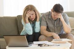 Finanzas calculadoras del hogar de los pares maduros preocupantes en el sofá fotos de archivo libres de regalías