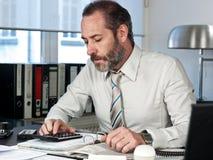 Finanzas calculadoras del hombre de negocios imagenes de archivo
