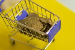 Finanzas, carretilla con las monedas del metal en background66 amarillo fotografía de archivo