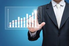 Finanzas derechas del gráfico del tacto de la mano de la postura del hombre de negocios aisladas en fondo azul fotografía de archivo libre de regalías