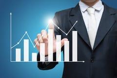 Finanzas derechas del gráfico del tacto de la mano de la postura del hombre de negocios aisladas encendido sobre fondo azul Imágenes de archivo libres de regalías