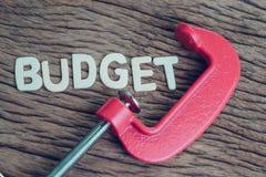 Finanzas, economía e idea del negocio, abrazadera roja que exprime alfabeto Foto de archivo