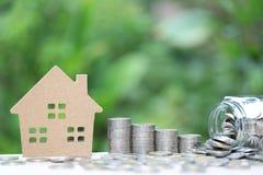 Finanzas, pila de dinero de las monedas y casa modelo en fondo verde natural, la inversi?n empresarial y propiedades inmobiliaria fotografía de archivo