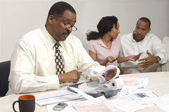 Finanzberater, der den Ausgaben-Empfang mit Paaren im Hintergrund hält Stockfoto