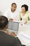 Finanzberater, der Laptop mit Paaren in der Diskussion über Dokumenten verwendet Stockbilder