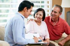 Finanzberater, der zu Hause mit älteren Paaren spricht Stockfotografie