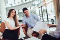Finanzberatervertretungsbericht zu den jungen Paaren f?r ihre Investition Verk?ufer und positive Paare, die ?ber Kauf sprechen lizenzfreie stockbilder