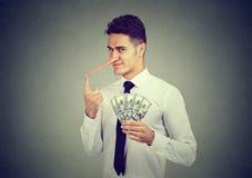 Finanzbetrugskonzept Junger Geschäftsmann des schlauen Lügners mit Dollarbargeld lizenzfreie stockfotografie