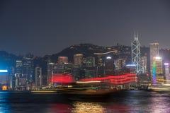 Finanzbezirk Kong Kong mit einem Boot, das in Front überschreitet Lizenzfreies Stockfoto