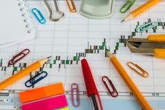 Finanzdiagramm auf einem weißen Hintergrund, Münzen, Stiften, Bleistiften und Büroklammern Lizenzfreies Stockfoto