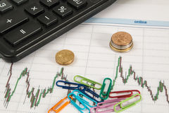 Finanzdiagramm auf einem weißen Hintergrund mit Taschenrechner, Münzen, Stifte, Bleistifte, Büroklammern Stockfotografie