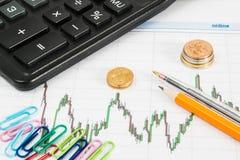Finanzdiagramm auf einem weißen Hintergrund mit Taschenrechner, Münzen, Stifte, Bleistifte, Büroklammern Lizenzfreies Stockfoto