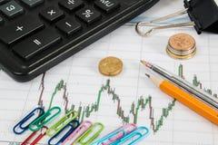 Finanzdiagramm auf einem weißen Hintergrund mit Taschenrechner, Münzen, Stifte, Bleistifte, Büroklammern Stockfotos