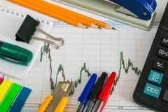Finanzdiagramm auf einem weißen Hintergrund mit Taschenrechner, Münzen, Stiften, Bleistiften und Büroklammern Stockfotos