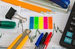 Finanzdiagramm auf einem weißen Hintergrund mit Taschenrechner, Münzen, Stiften, Bleistiften und Büroklammern Lizenzfreies Stockbild