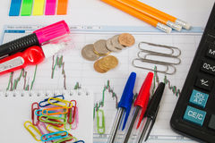 Finanzdiagramm auf einem weißen Hintergrund mit Taschenrechner, Münzen, Stiften, Bleistiften und Büroklammern Stockbild