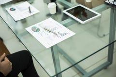 Finanzdiagramm, Gläser und Stift auf dem Arbeitsplatz des Geschäftsmannes Lizenzfreie Stockbilder